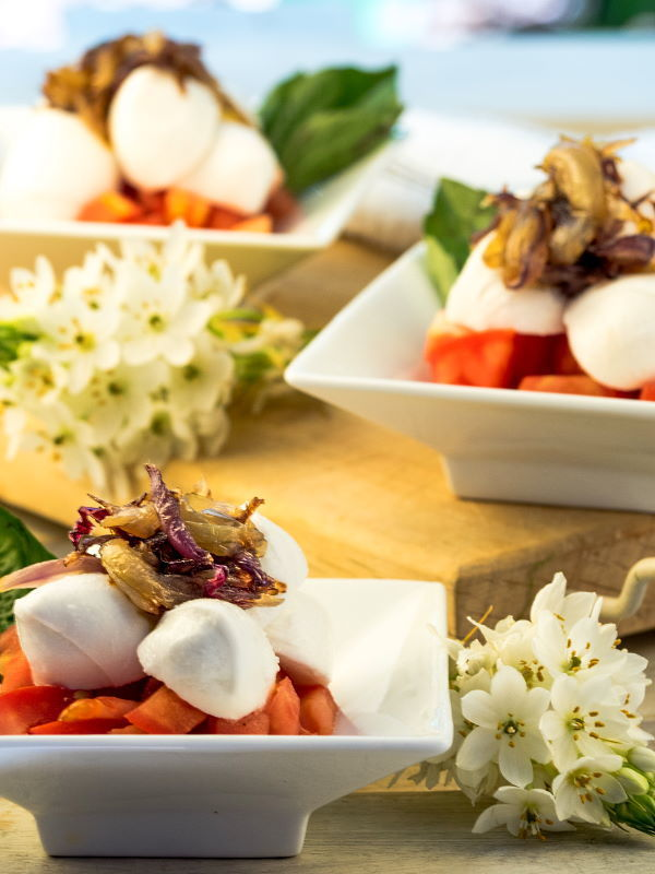 Bocconcini Caprese with Cherry Tomatoes on serving dishes and flowers in the background.
