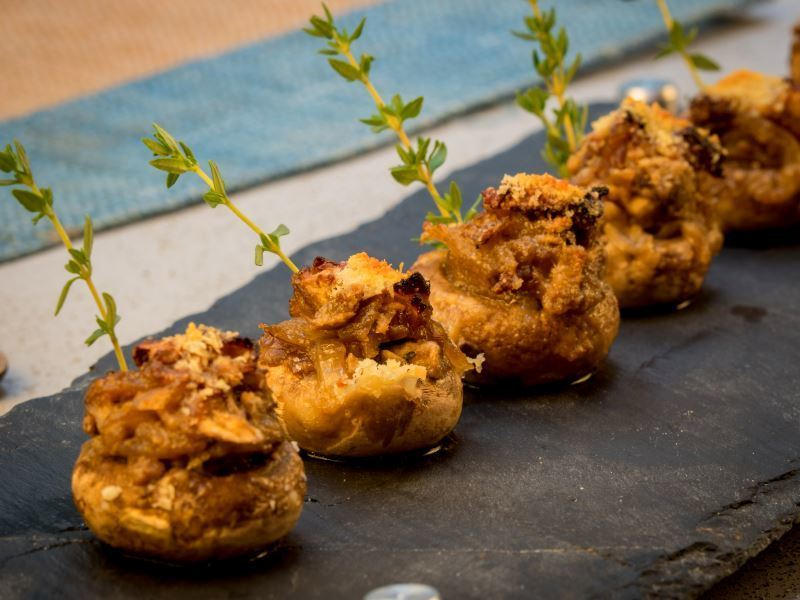 Crispy Button Mushrooms with Herbs & Melted Cheese on a granite serving platter.