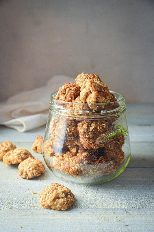Electric Skillet Oatmeal Cookies in a clear jar, on white wooden background.