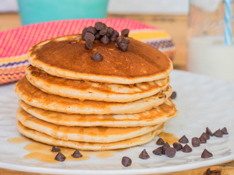 Pancakes piled on a plate with chocolate chips and maple syrup.