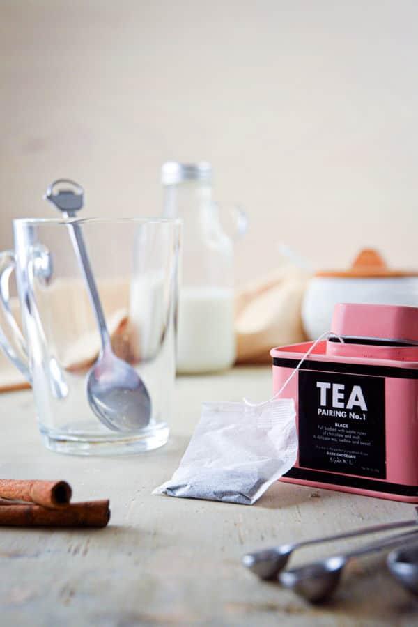 Earl grey tea, clear glass mug, mixing spoon, cinnamon on wooden background.