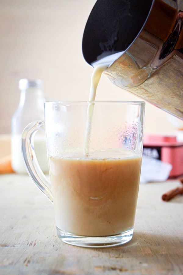 Hot milk and a london fog in a clear glass mug.