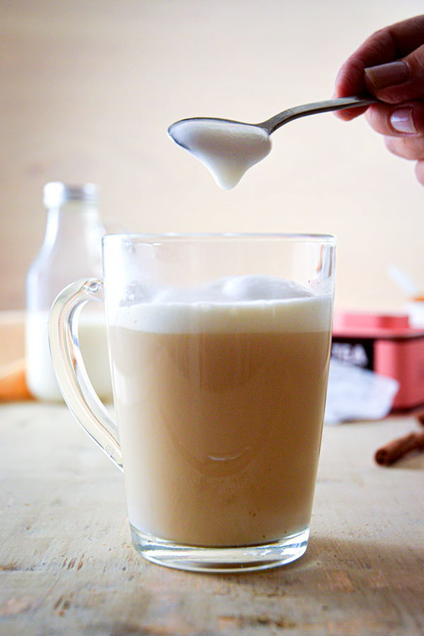 A spoon of frothy milk and a london fog in a clear glass mug.