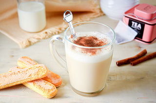 London Fog in a clear glass mug, biscuits, cinnamon and tea bag on the side
