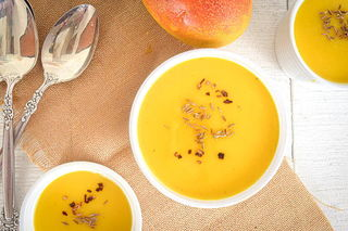 Mango soup in white bowls, 2 spoons and a fresh mango on a brown piece of cloth, white wooden background.