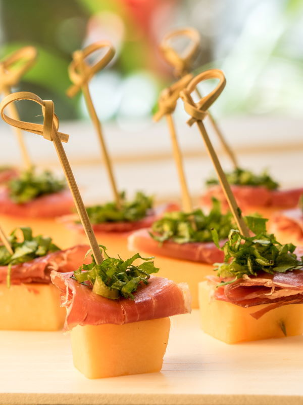 Melon & Prosciutto Skewers with greens on a serving platter.