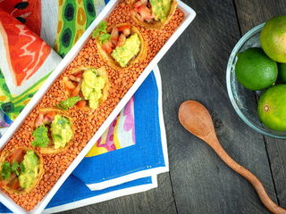 Mexican Tortilla Baskets on a serving tray with a bowl of limes and wooden spoon.