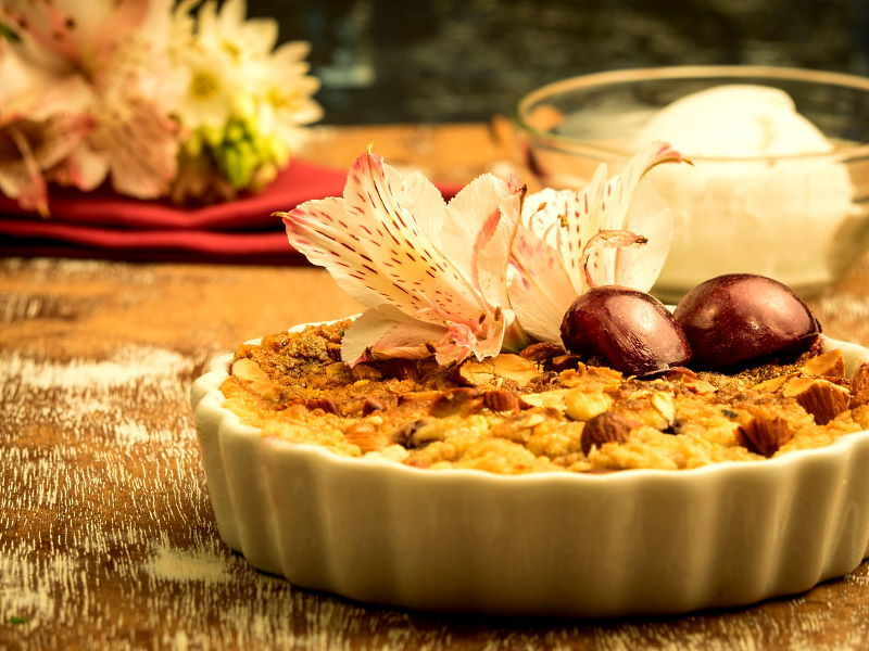 Plum Crumble with Vanilla Ice Cream in a tart dish with flowers in the background.