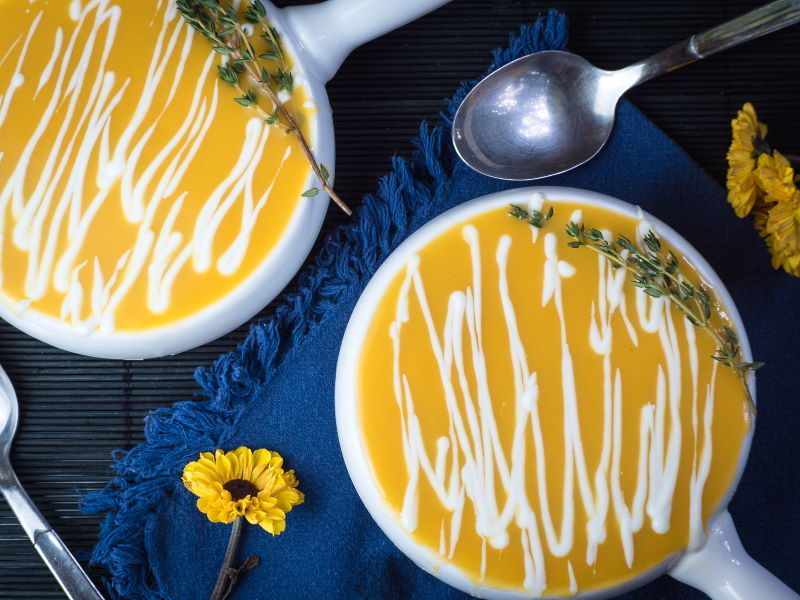 Pumpkin Cream Soup with Orange & Drizzled Yogurt Dressing, on blue cloth.