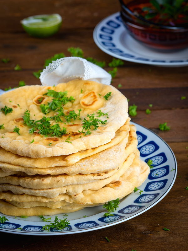 Pumpkin & Garlic Naan Bread piled on a plate.