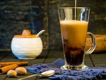 Coffee cream pouring into a mug with cinnamon sticks and sugar jar in the background.