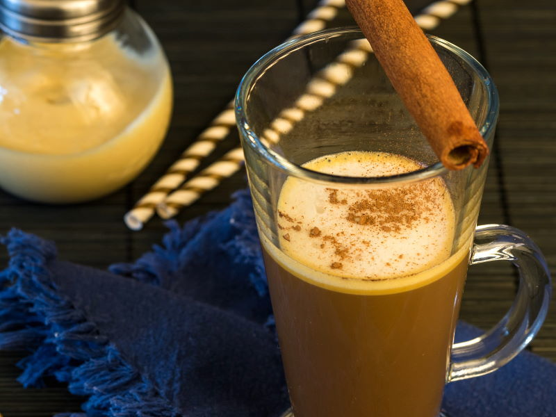 Coffee with pumpkin spice cream and a cinnamon stick.
