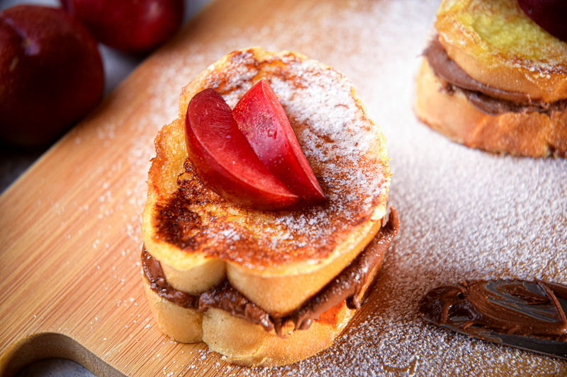 Nutella stuffed French toast on wooden cutting board.