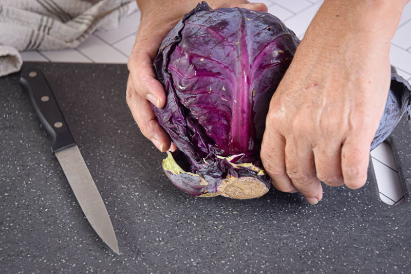 Red cabbage and knife on cutting board.
