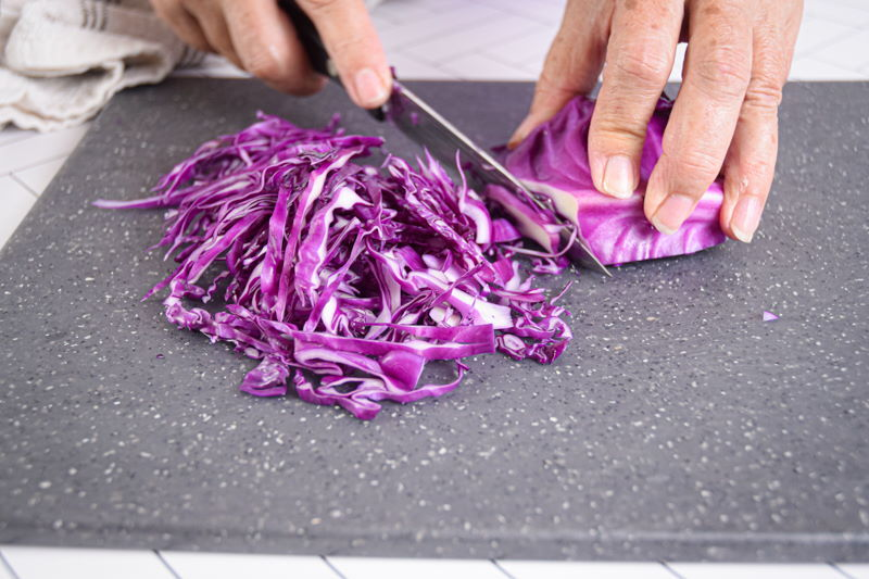 Red cabbage and knife on cutting board, getting shredded.