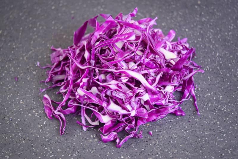 Shredded cabbage on dark speckled cutting board.