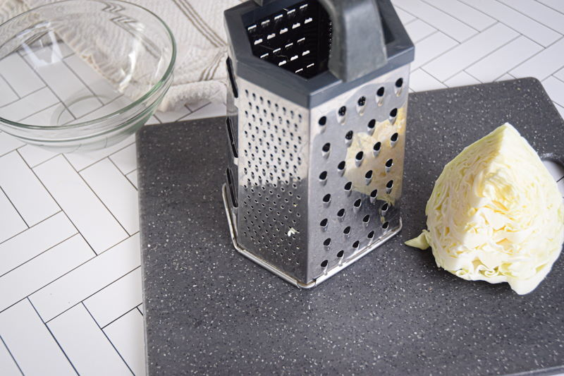 Grater and white cabbage on dark cutting board.