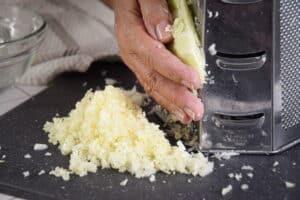 Shredding white cabbage with box grater on dark cutting board.