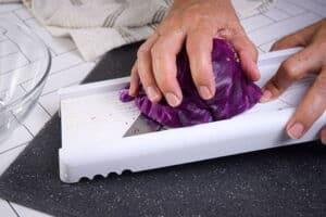 Shredding red cabbage with mandolin on dark cutting board.