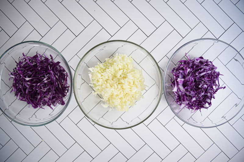 Three bowls each with shredded cabbage on white background.