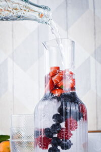 A glass pitcher filled with ice and berries.