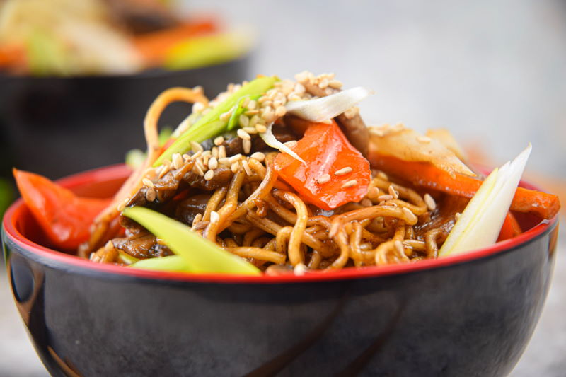 Chicken and vegetable lo mein in red and black bowl.