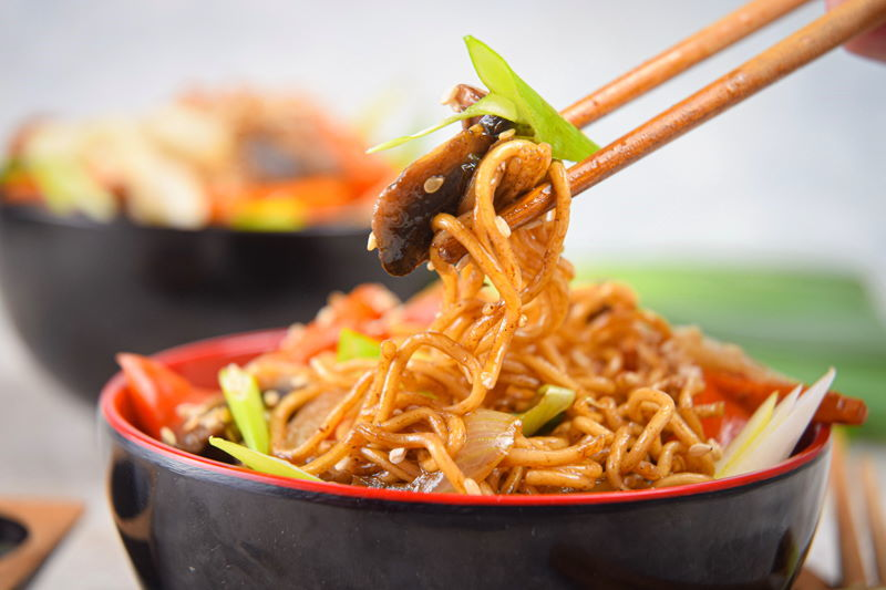 Chicken and vegetable lo mein in red and black bowls, with chopsticks.