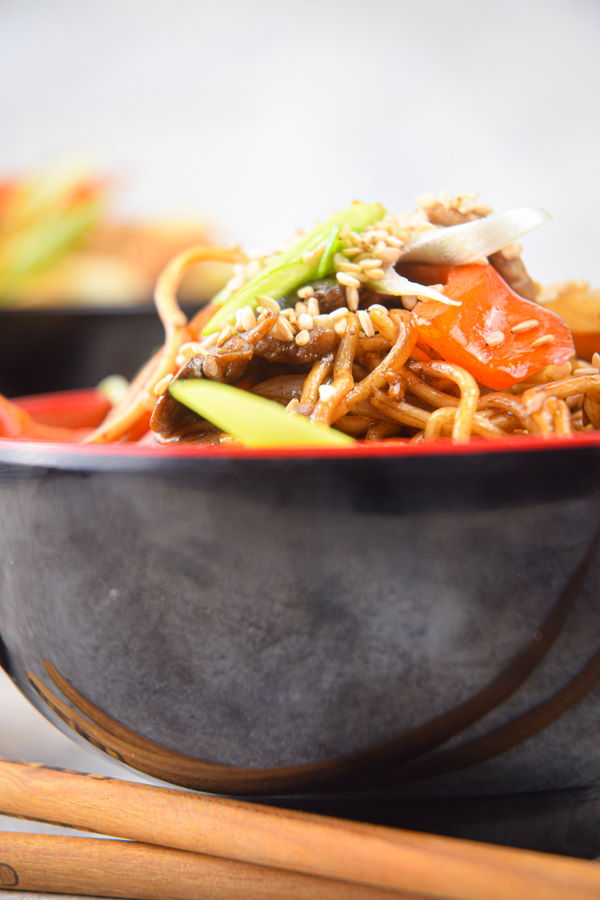Chicken and vegetable lo mein in red and black bowl, with chopsticks.