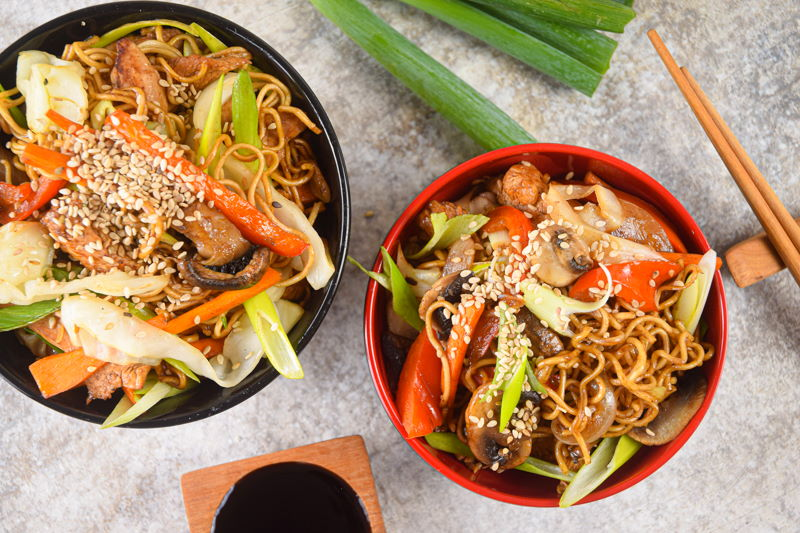 Chicken and vegetable lo mein in red and black bowls, chopsticks and green onions on the side.
