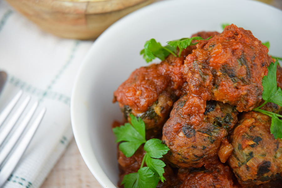 Turkey and mushroom meatballs with tomato sauce in a white bowl.