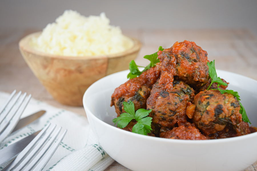 Turkey and Mushroom Meatballs in a white bowl, white rice in a wooden bowl in the background.