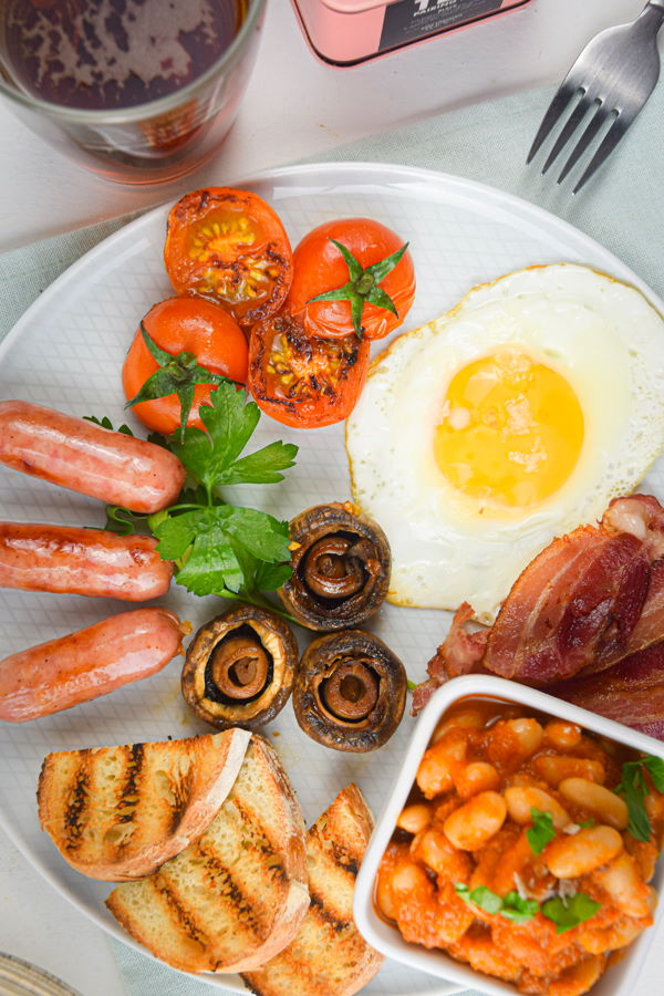 Electric Skillet Full English Breakfast on a white plate, tea on the side.