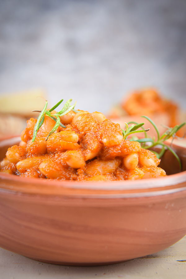 British Baked beans in tomato sauce in a rust-colored bowl, toasted bread on the side.