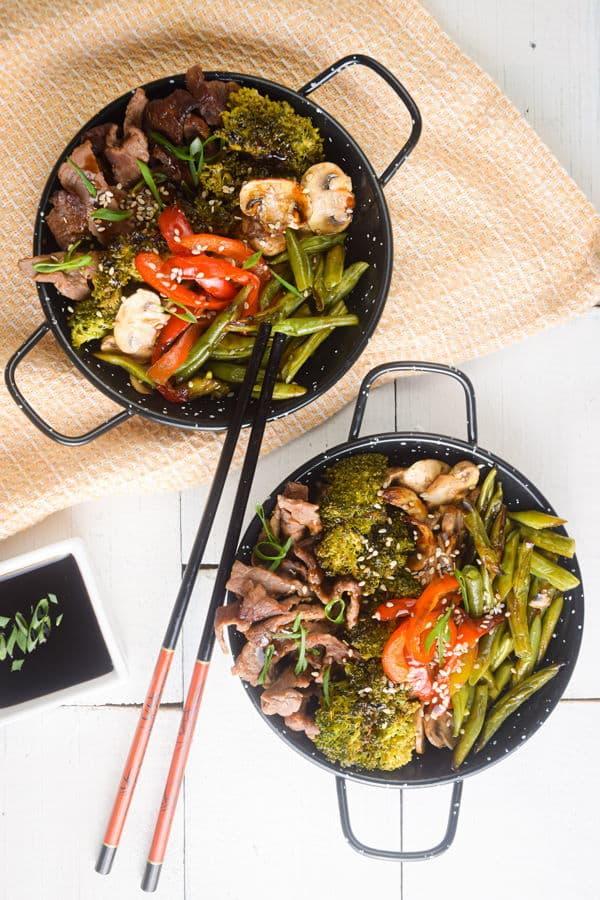 Beef teriyaki in a black ramen bowl, chopsticks on the side.