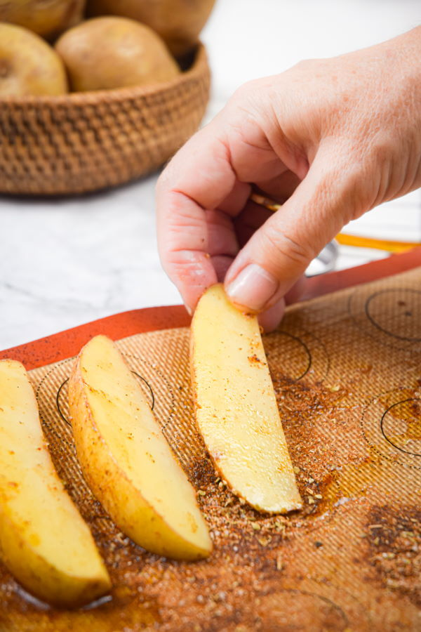Sliced potatoes placed on silicone mat.