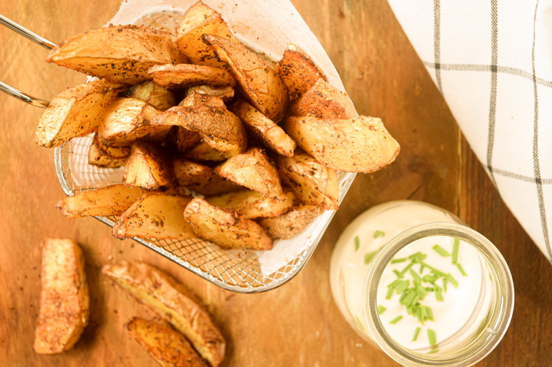 Cajun fries in a wire basket, ranch sauce in a jar in the background.