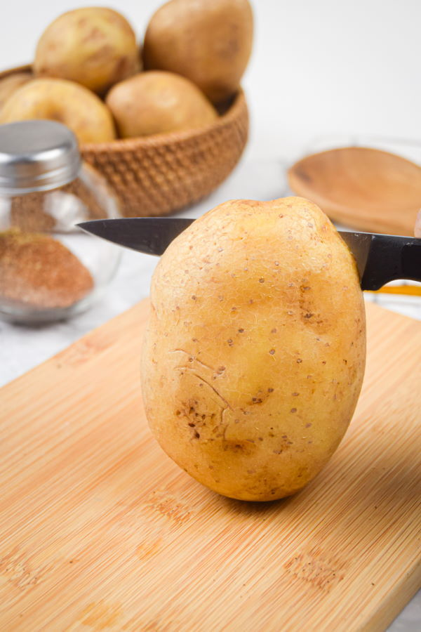 A potato on a wooden cutting board, potatoes in the background.