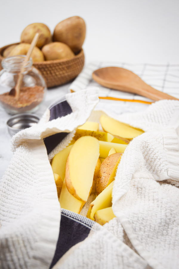 A towel over potato slices. potatoes in the background.