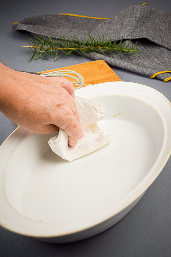 Wiping down a baking dish, blue-grey background.