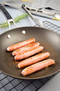 Sausages in a frying pan.
