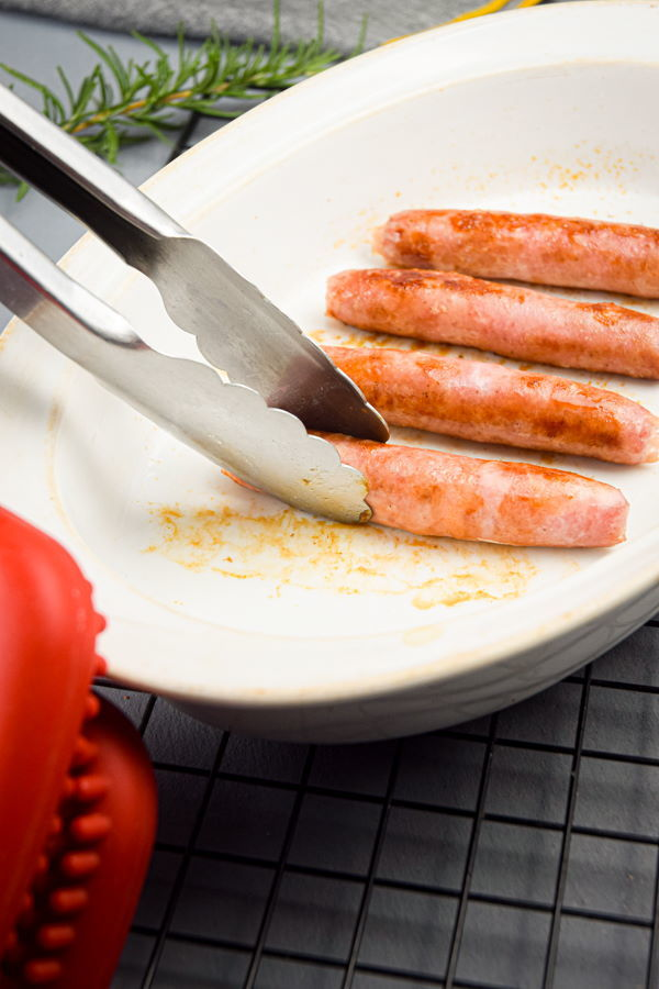 Sausages in a baking dish on metal rack.