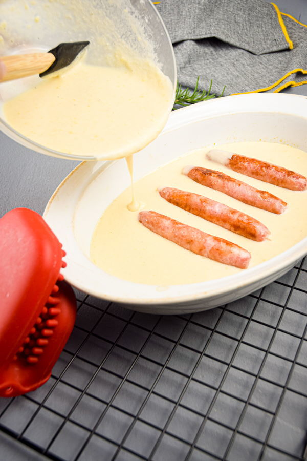 Toad in the hole batter and sausages in a baking dish on metal rack.