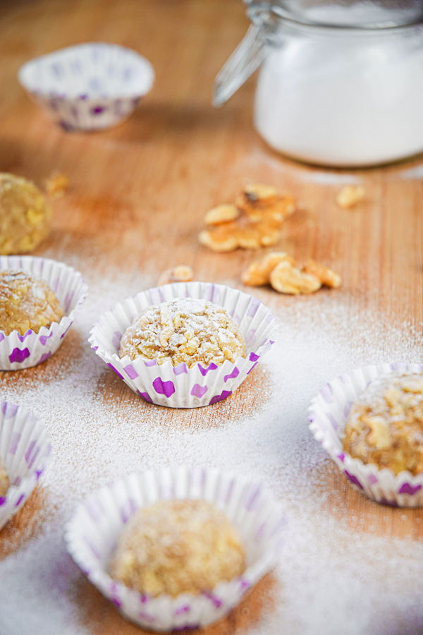 Marzipan Nut Balls in purple and white baking cups, on wooden background.