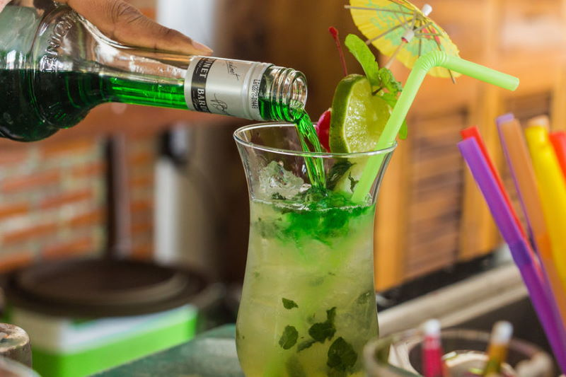Green cocktail with umbrella.