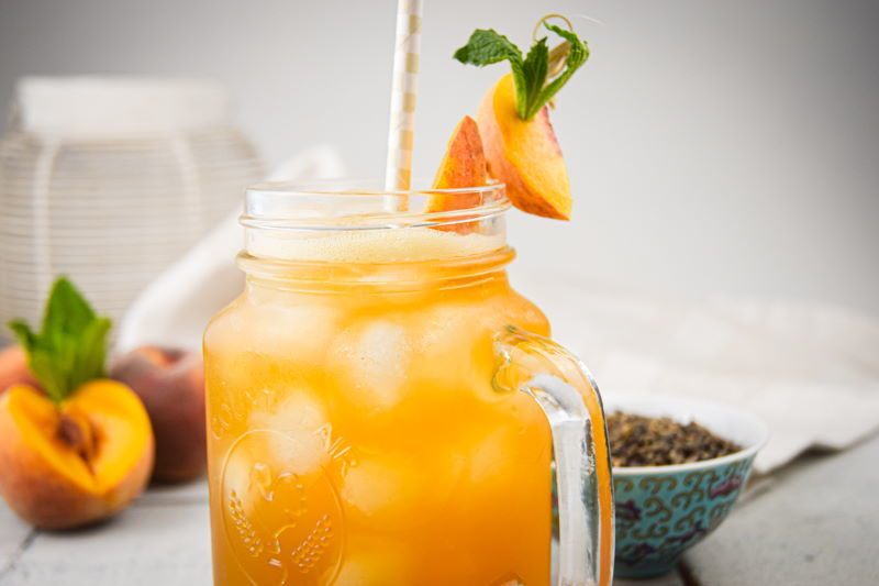 Peachy Iced Green Tea in a mason jar glass, a small bowl of tea leaves and peaches on the side.
