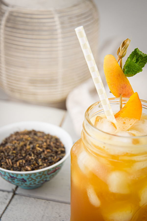 Peachy Iced Green Tea in a mason jar glass, a small bowl of tea leaves on the side.