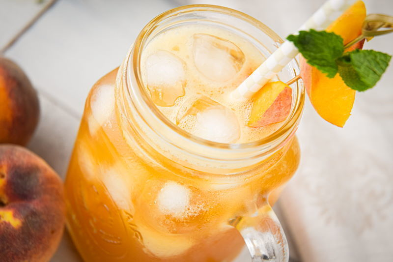 Peachy Iced Green Tea in a mason jar glass, a small bowl of peaches on the side.