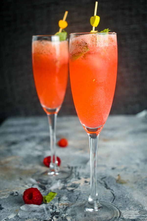 Raspberry twist cocktail with mint and lemon twist in a champagne flute.