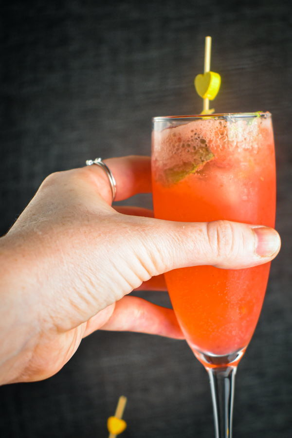 Raspberry twist cocktail with mint and lemon twist in a champagne flute, in a woman's hand.