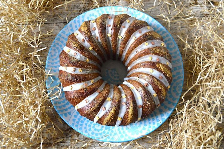 Marzipan bundt cake on blue plate, wooden background.